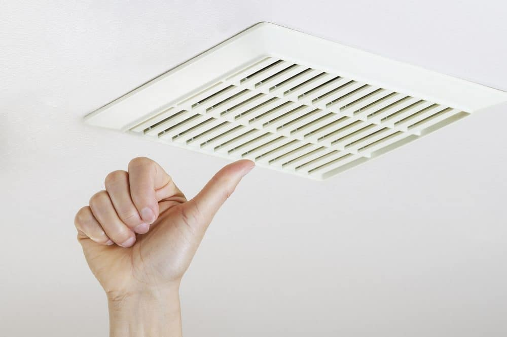 Close up horizontal photo of female hand giving thumbs up after cleaning and installing bathroom fan vent cover from ceiling