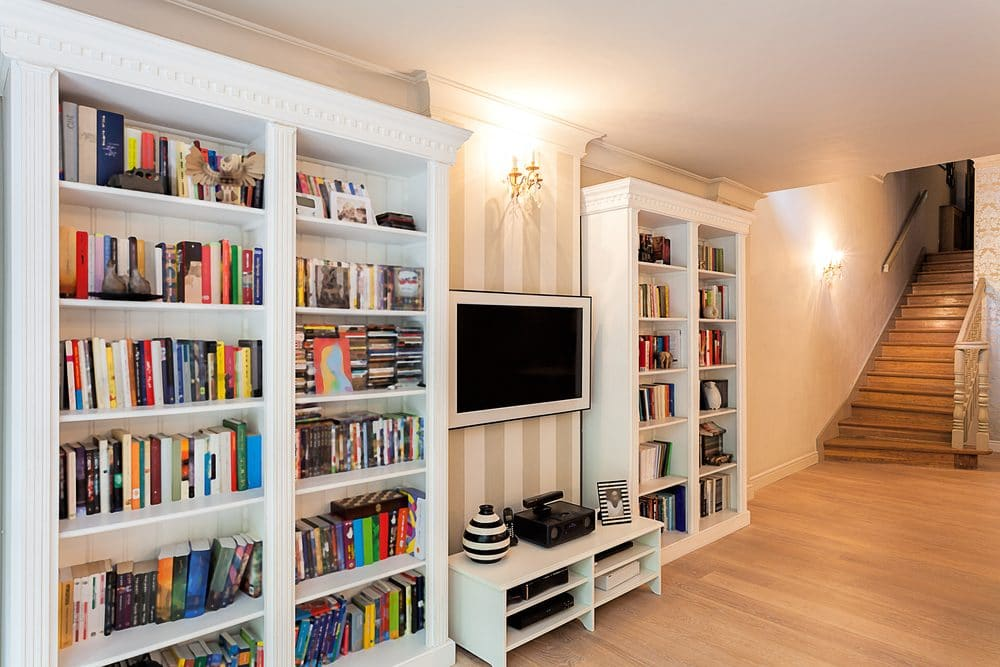 A living room with a bookshelf and entertainment center.