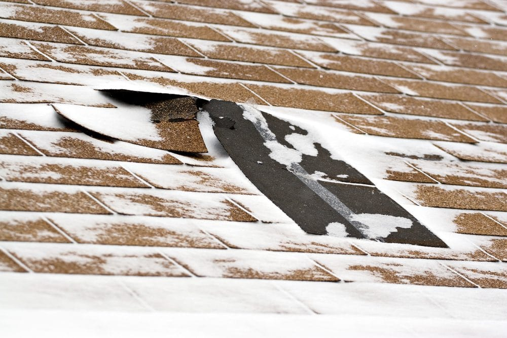 Damaged roof shingles blown off a home from a windy winter storm with strong winds. You want to fix this to prevent leaks and water damage.