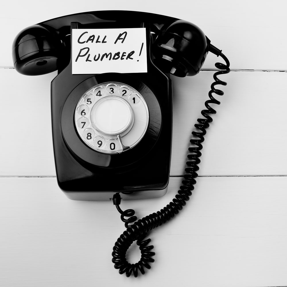 "A rotary telephone with a sign that says ""Call a Plumber to Prevent Water Leaks and Water Damage In Your Home."""