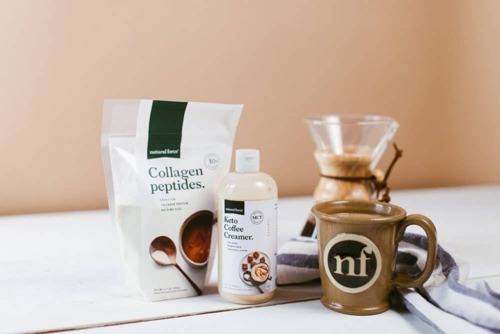 Natural force mold and mycotoxin free coffee, natural force collegen peptide, natural force MTC oil, a natural force coffee mug, and a pourover carafe on a tan background