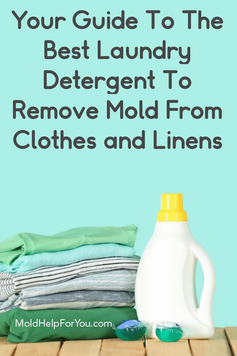 A bottle of DIY laundry detergent to remove mold from clothes and linens. It is next to a pile of clean towels against an aqua background